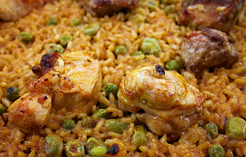 Paella with chicken, pork chops,  broad beans and peas